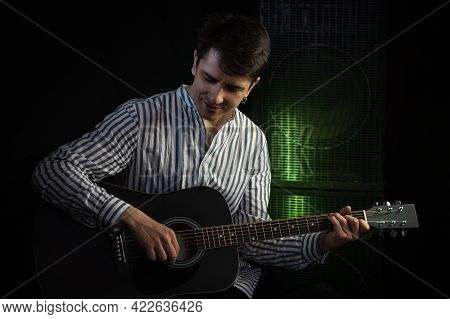 Photo Of Man Sitting And Playing Acoustic Guitar In Recording Studio On Dark Background With Light E