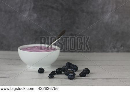 Healthy Eating Concept - A Bowl Of Blueberry Yoghurt And A Pile Of Berries On Wooden Background