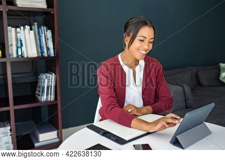 Portrait of mature executive businesswoman using digital tablet while working from home. African mature woman working on laptop at home. Happy smiling mid adult woman making notes in smart working.
