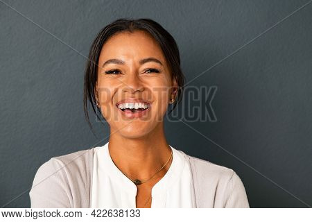 Close up face of beautiful mature woman looking at camera with big laugh. Mid adult hispanic woman standing isolated against grey wall while having fun. Portrait of smiling indian lady laughing.