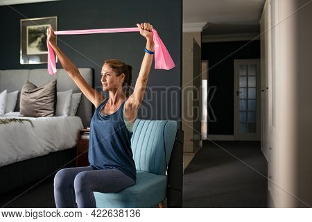 Middle aged determined woman sitting on armchair using resistance band. Mid adult fitness woman exercising for muscles of the chest at home during lockdown. Healthy mature lady working out in bedroom.