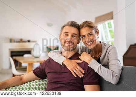 Middle aged couple embracing on sofa while looking at camera. Mature happy woman embracing her husband from behind while relaxing at home. Portrait of smiling wife and man loving in perfect harmony.