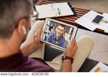 Mature businessman talking with colleague during video call on digital tablet. Mid adult business man working from home in conversation with colleague during online meeting.