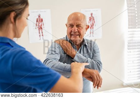 Physiotherapist helping senior man with elbow exercise in clinic. Doctor checking elbow of senior patient. Old man during an appointment with professional osteopath working and massaging his shoulder.