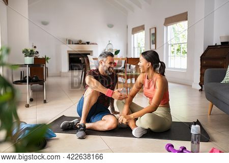 Happy indian man with african woman talking after fitness workout at home. Mature mixed race coach talking to trainee during break. Middle aged couple laughing after workout in their living room.