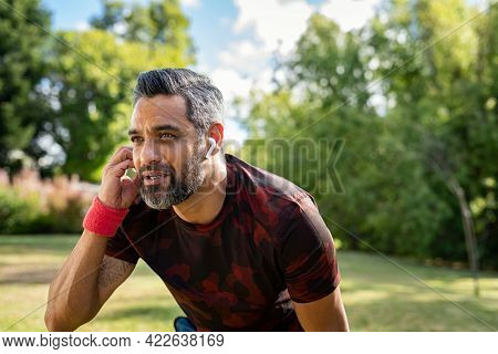 Portrait of mixed race sports man resting after run at park with copy space while listening to music. Middle adult indian jogger adjusting wireless earphone while running outdoor. Active mature man.