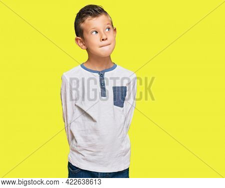 Adorable caucasian kid wearing casual clothes smiling looking to the side and staring away thinking.