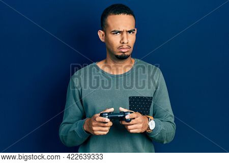 Young african american man playing video game holding controller skeptic and nervous, frowning upset because of problem. negative person.
