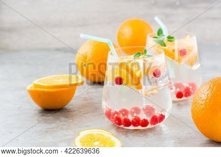 Hard Seltzer Cocktail With Orange, Cranberry And Mint In Glasses And Cut Oranges On The Table. Alcoh