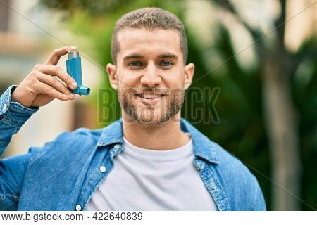 Young caucasian asthmatic man smiling happy holding inhaler at the park.