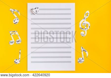 Blank Sheet Music, Music Notes And Hearts Cut From Music Text On Yellow Background. Top View