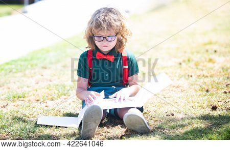 Smart Curious Nerd In Glasses Reading Book Study With Copybook Outdoor, Back To School