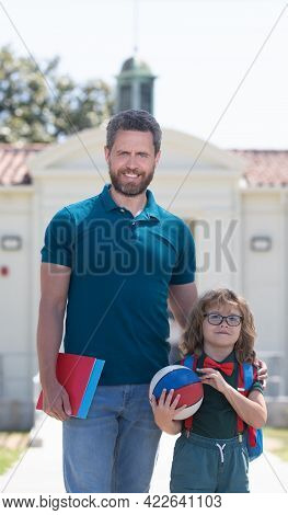 Happy Father With Nerd Son In Glasses Hold Ball And Book First Day At School, Family Values.