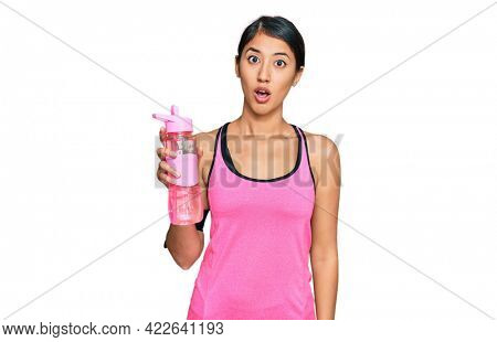 Beautiful asian young sport woman wearing sportswear drinking bottle of water scared and amazed with open mouth for surprise, disbelief face