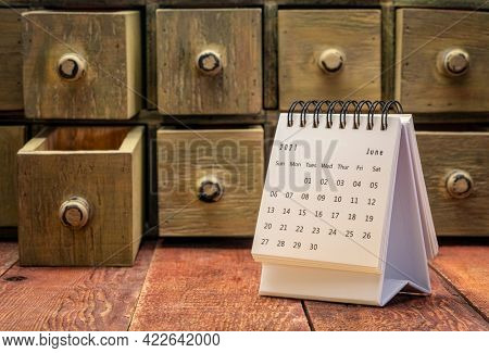 June 2021 - spiral desktop calendar on a weathered barn wood table with rustic apothecary drawers in background, time and business concept