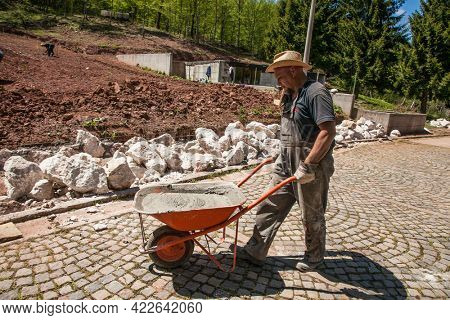 Sarajevo , Bosnia-May 11, 2021: Construction worker pushing wheelbarrow with concrete at building a engineer on construction. Bosnia and Herzegovina.