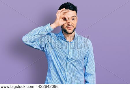 Hispanic man with beard wearing casual business shirt doing ok gesture with hand smiling, eye looking through fingers with happy face.