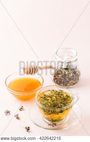 Fresh Hot Tea With Oregano In A Cup, Honey In A Bowl And Dry Herb In A Jar. Herbal Medicine And Alte