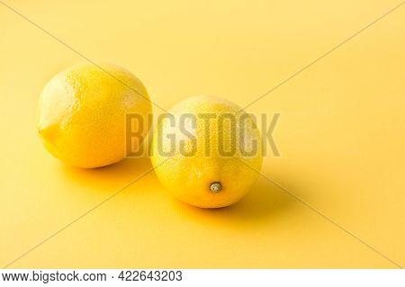 Two Ripe Whole Lemons On A Yellow Background. Detox Fruit Diet, Body Detoxification