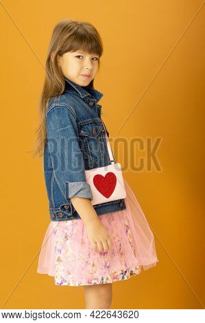 Beautiful Girl In Stylish Outfit With Shoulder Bag. Smiling Emotional Preteen Girl Wearing Denim Jac