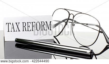 Text Tax Reform On Paper On Light Background With Pen And Glasses. Business