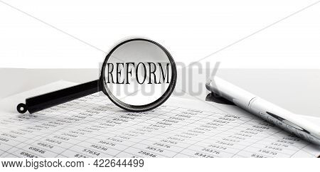 Magnifying Glass With Text Reform On Background With Pen