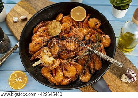 Fried Unpeeled Shrimp. Served In A Rustic-style Frying Pan. Roasted Garlic Spices And Lemon.