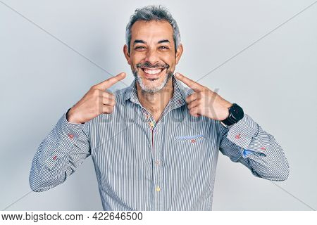 Handsome middle age man with grey hair pointing mouth with fingers smiling and laughing hard out loud because funny crazy joke.
