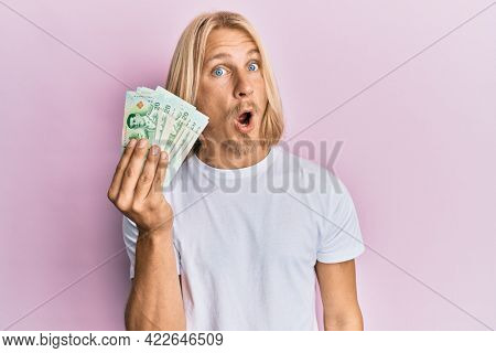 Caucasian young man with long hair holding 20 thai baht banknotes scared and amazed with open mouth for surprise, disbelief face