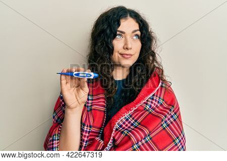 Young brunette woman with curly hair wrapped in a blanket holding thermometer smiling looking to the side and staring away thinking.