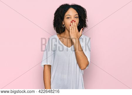 Young african american girl wearing casual clothes bored yawning tired covering mouth with hand. restless and sleepiness.