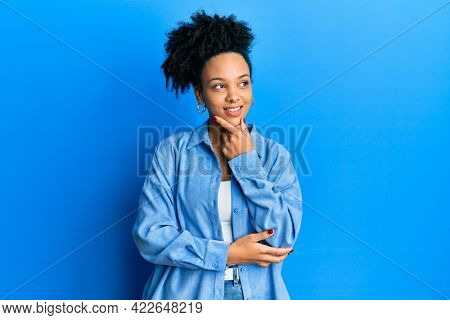 Young african american girl wearing casual clothes with hand on chin thinking about question, pensive expression. smiling with thoughtful face. doubt concept.