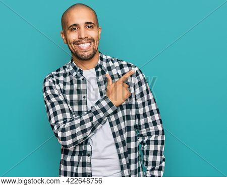 Hispanic adult man wearing casual clothes cheerful with a smile of face pointing with hand and finger up to the side with happy and natural expression on face