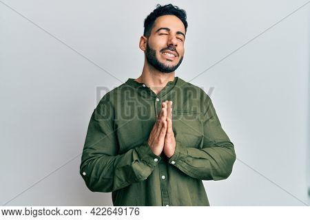 Young hispanic man wearing casual clothes begging and praying with hands together with hope expression on face very emotional and worried. begging.