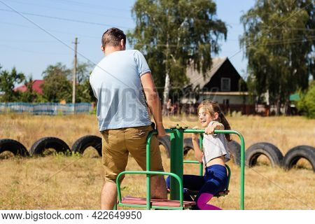 Defocus Emotion Preteen Girl Riding A Carousel On Playground With Young Man, Guy, Her Older Brother