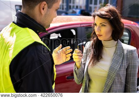 Policeman Doing Driver Alcohol Test Using Breathalyzer
