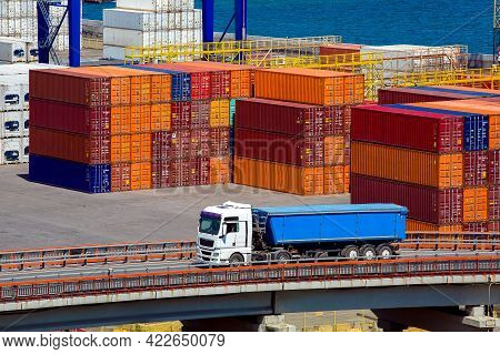 A Long-length Truck Transports Goods Over A Road Bridge From A Marine Warehouse Of Colored Container