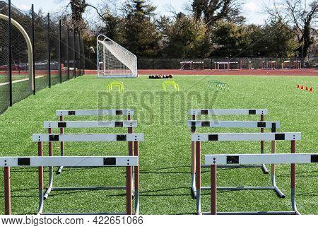 Track Hurdles, Mini Hurdles Medicine Balls And Orange Cones Set Up On A Green Turf Field For Track A