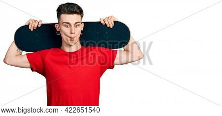 Young caucasian boy with ears dilation holding skate over shoulders making fish face with mouth and squinting eyes, crazy and comical.