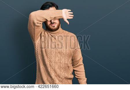 Young hispanic man wearing casual clothes covering eyes with arm, looking serious and sad. sightless, hiding and rejection concept