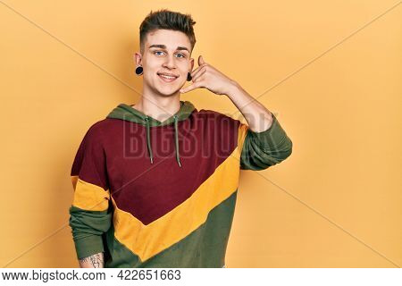Young caucasian boy with ears dilation wearing casual sweatshirt smiling doing phone gesture with hand and fingers like talking on the telephone. communicating concepts.
