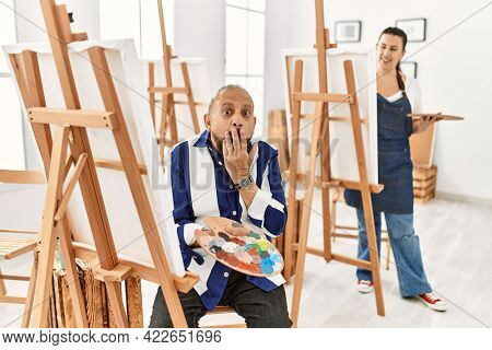 Senior artist man at art studio laughing and embarrassed giggle covering mouth with hands, gossip and scandal concept