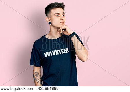 Young caucasian boy with ears dilation wearing volunteer t shirt with hand on chin thinking about question, pensive expression. smiling with thoughtful face. doubt concept.