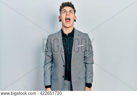 Young caucasian boy with ears dilation wearing business jacket angry and mad screaming frustrated and furious, shouting with anger. rage and aggressive concept.