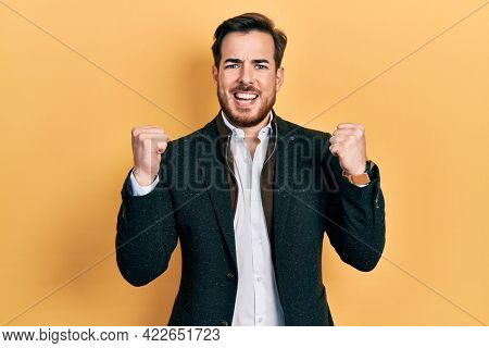 Handsome caucasian man with beard wearing elegant business jacket screaming proud, celebrating victory and success very excited with raised arms