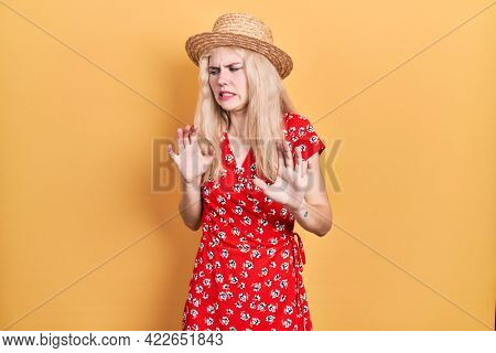 Beautiful caucasian woman with blond hair wearing summer hat disgusted expression, displeased and fearful doing disgust face because aversion reaction. with hands raised