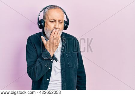 Handsome senior man with beard listening to music using headphones bored yawning tired covering mouth with hand. restless and sleepiness.