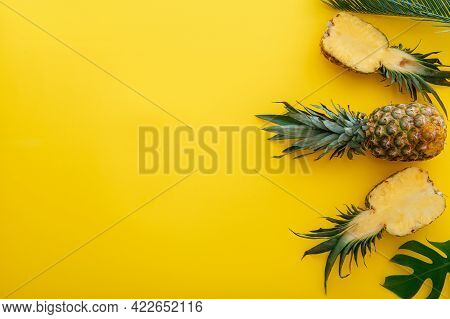 Pineapples And Palm Leaves On Yellow Color Summer Background. Whole Tropical Summer Pineapples Fruit