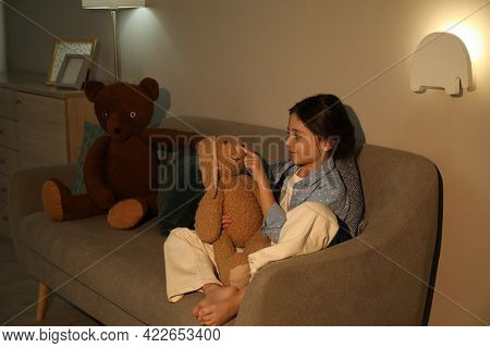 Little Girl With Toy Bunny In Living Room Lit By Night Lamp