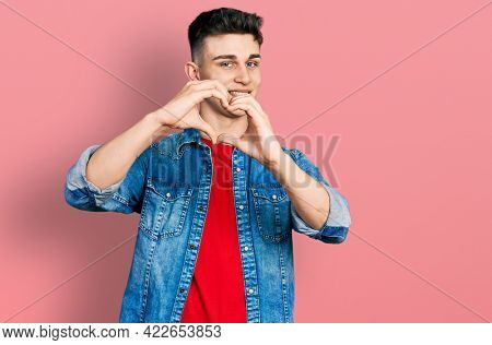 Young caucasian boy with ears dilation wearing casual denim jacket smiling in love doing heart symbol shape with hands. romantic concept.